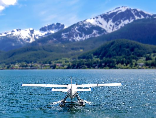 Small plane on the water with mountains in the background