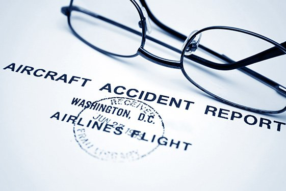 Aircraft accident report with glasses on paperword